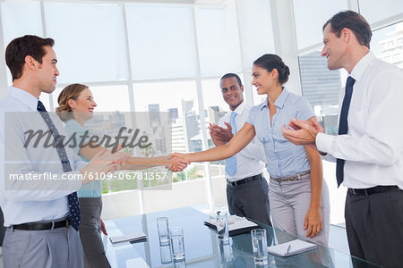 Business people clapping their hands between colleagues Stock Photo - Premium Royalty-Free, Image code: 6109-06781357