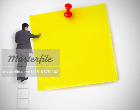 Businessman standing on ladder writing on large yellow note Stock Photo - Premium Royalty-Free, Image code: 6109-06781462