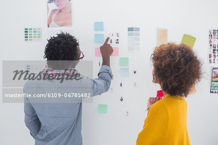 Designers pointing at a photo Stock Photo - Premium Royalty-Free, Image code: 6109-06781482