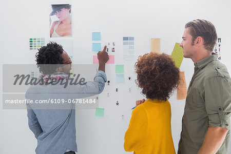 Team of designers pointing at a group of photos Stock Photo - Premium Royalty-Free, Image code: 6109-06781484