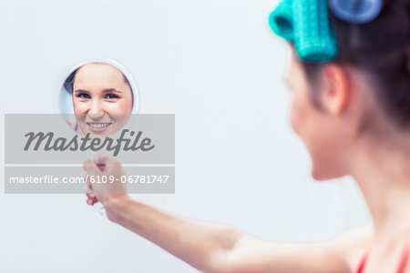 Young woman holding a mirror Stock Photo - Premium Royalty-Free, Image code: 6109-06781747