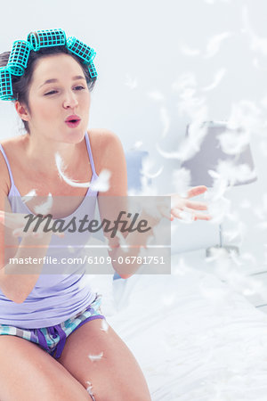 Pretty woman blowing feathers in her bedroom Stock Photo - Premium Royalty-Free, Image code: 6109-06781751