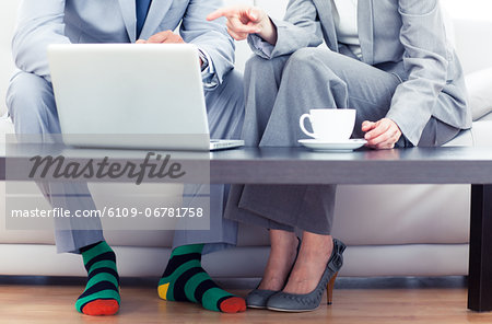 Business people sitting on a couch Stock Photo - Premium Royalty-Free, Image code: 6109-06781758