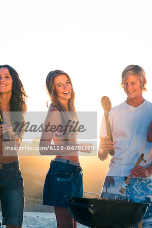 Smiling friends cooking barbecue on the beach Stock Photo - Premium Royalty-Free, Image code: 6109-06781769