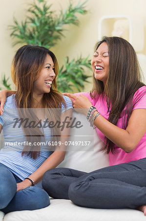 Two laughing sisters sitting on a couch in the living room Stock Photo - Premium Royalty-Free, Image code: 6109-07497137