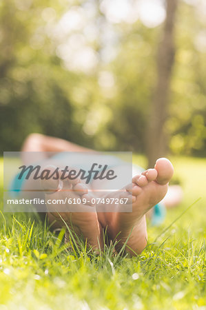 Close up of female feet lying on grass in nature Stock Photo - Premium Royalty-Free, Image code: 6109-07497267
