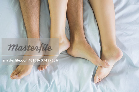 Peaceful couple cuddling in their bed in the bedroom Stock Photo - Premium Royalty-Free, Image code: 6109-07497306