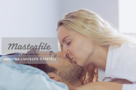 Intimate young couple kissing each other lying in the bed Stock Photo - Premium Royalty-Free, Image code: 6109-07497311