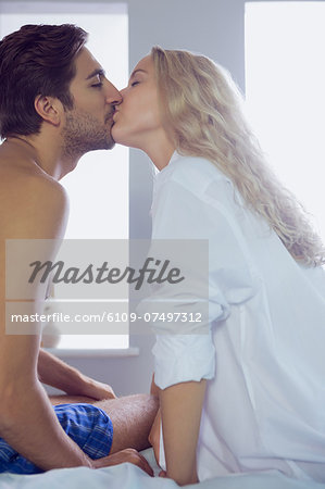 Attractive couple kissing each other sitting on their bed in the bedroom Stock Photo - Premium Royalty-Free, Image code: 6109-07497312