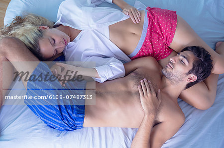 Attractive young couple sleeping in their bed in the bedroom Stock Photo - Premium Royalty-Free, Image code: 6109-07497313