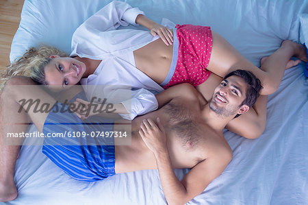 Attractive young couple lying on their bed looking at the camera Stock Photo - Premium Royalty-Free, Image code: 6109-07497314