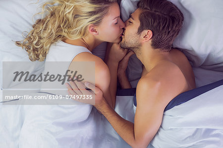 Cute young couple kissing each other while lying in their bed Stock Photo - Premium Royalty-Free, Image code: 6109-07497335