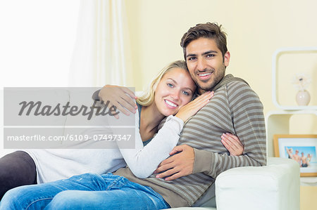 Sweet young couple sitting on a couch smiling at the camera Stock Photo - Premium Royalty-Free, Image code: 6109-07497347