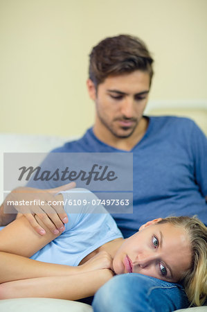 Thoughtful woman lying on a couch having her head on the lap of her boyfriend Stock Photo - Premium Royalty-Free, Image code: 6109-07497363