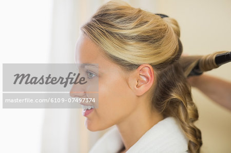 Blonde cute woman having her hair done wearing a bath robe Stock Photo - Premium Royalty-Free, Image code: 6109-07497374