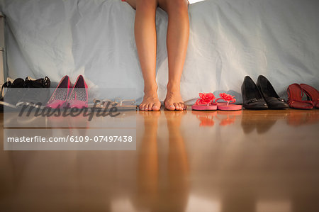 Woman sitting on edge of bed beside large variety of shoes at home in bedroom Stock Photo - Premium Royalty-Free, Image code: 6109-07497438