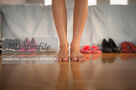 Woman standing in front of large variety of shoes at home in bedroom Stock Photo - Premium Royalty-Free, Image code: 6109-07497439