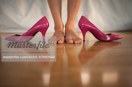 Woman standing beside bright pink high heels at home in bedroom Stock Photo - Premium Royalty-Free, Image code: 6109-07497440