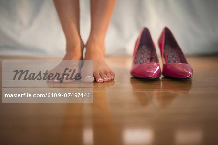 Woman standing beside pink high heels at home in bedroom Stock Photo - Premium Royalty-Free, Image code: 6109-07497441