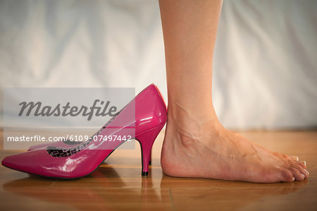 Woman standing beside fun pink high heels at home in bedroom Stock Photo - Premium Royalty-Free, Image code: 6109-07497442