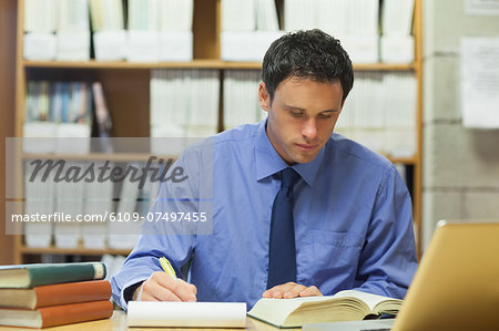 Calm librarian taking notes of a book in library in a college Stock Photo - Premium Royalty-Free, Image code: 6109-07497455