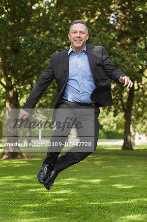 Joyful professor clicking his heels on campus at the university Stock Photo - Premium Royalty-Free, Image code: 6109-07497720