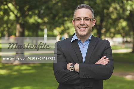 Happy professor looking at camera with arms folded on campusat the university Stock Photo - Premium Royalty-Free, Image code: 6109-07497723