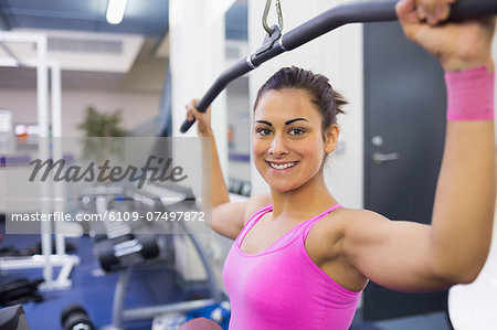 Smiling woman exercising on weight machine in weights room of gym Stock Photo - Premium Royalty-Free, Image code: 6109-07497872