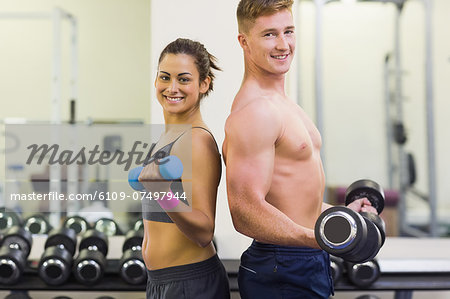 Topless man and smiling woman holding dumbbells in weights room of gym Stock Photo - Premium Royalty-Free, Image code: 6109-07497944