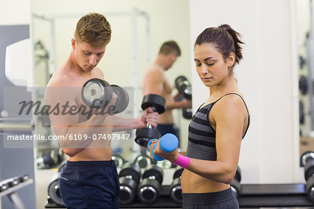 Determined man and woman holding dumbbells in weights room of gym Stock Photo - Premium Royalty-Free, Image code: 6109-07497947