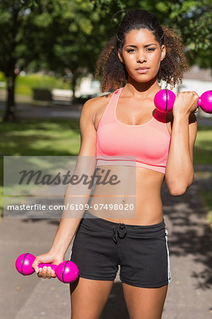 Portrait of a fit young woman exercising with dumbbells in the park Stock Photo - Premium Royalty-Free, Image code: 6109-07498020