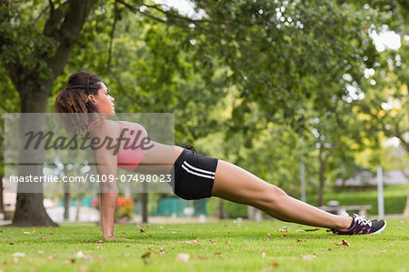 Full length side view of a toned young woman doing stretching exercise in the park Stock Photo - Premium Royalty-Free, Image code: 6109-07498023