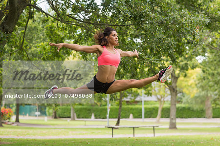 Full length of a toned young woman performing the splits jump in the park Stock Photo - Premium Royalty-Free, Image code: 6109-07498038