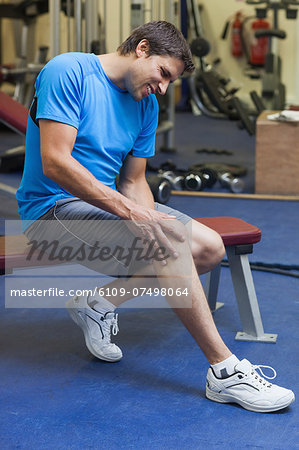 Side view of a healthy young man with an injured leg sitting in the gym Stock Photo - Premium Royalty-Free, Image code: 6109-07498064