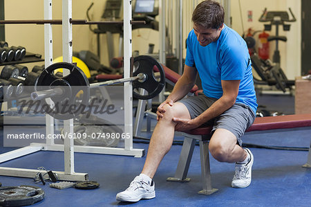 Full length of a healthy young man with an injured leg sitting in the gym Stock Photo - Premium Royalty-Free, Image code: 6109-07498065
