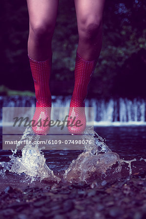 Close up low section of a woman in red gumboots jumping in water Stock Photo - Premium Royalty-Free, Image code: 6109-07498076