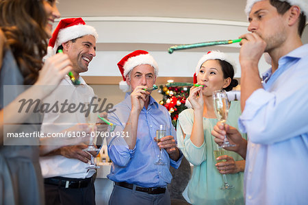 People in Santas hats with champagne flutes and noise makers Stock Photo - Premium Royalty-Free, Image code: 6109-07600931