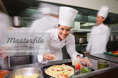 Happy chef preparing a pizza Stock Photo - Premium Royalty-Free, Image code: 6109-07601100