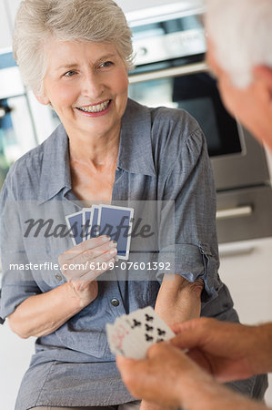 Happy senior couple playing a card game Stock Photo - Premium Royalty-Free, Image code: 6109-07601392
