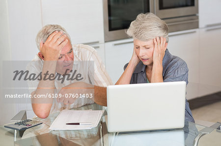 Worried senior couple using the laptop to pay bills Stock Photo - Premium Royalty-Free, Image code: 6109-07601403