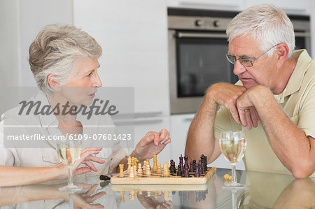 Smiling senior couple playing chess and having white wine Stock Photo - Premium Royalty-Free, Image code: 6109-07601423