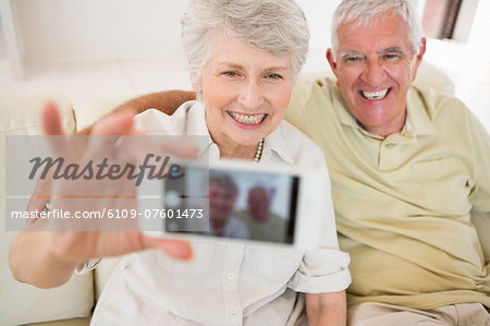Senior woman taking a selfie with her smartphone Stock Photo - Premium Royalty-Free, Image code: 6109-07601473