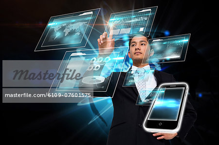 Asian businessman pointing to interface Stock Photo - Premium Royalty-Free, Image code: 6109-07601575
