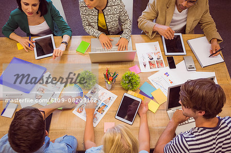 Creative colleagues with laptop and digital tablet office Stock Photo - Premium Royalty-Free, Image code: 6109-08203162