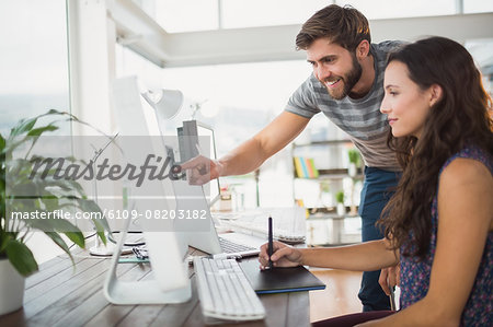 Smiling casual business team working together Stock Photo - Premium Royalty-Free, Image code: 6109-08203182