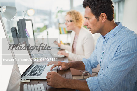 Smiling casual business team working together Stock Photo - Premium Royalty-Free, Image code: 6109-08203184