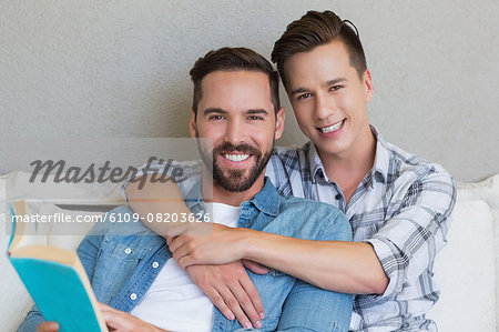 Homosexual couple men reading a book together Stock Photo - Premium Royalty-Free, Image code: 6109-08203626