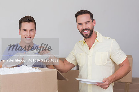 Happy homosexual couple unpacking box Stock Photo - Premium Royalty-Free, Image code: 6109-08203682