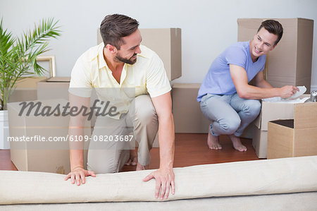 Handsome man unrolling carpet with his boyfriend behind Stock Photo - Premium Royalty-Free, Image code: 6109-08203687