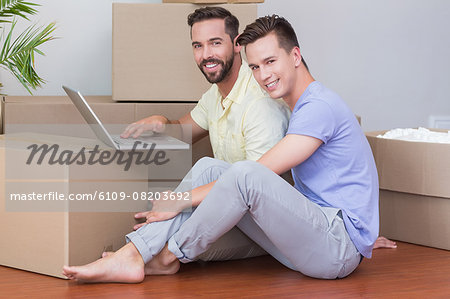 Happy homosexual couple looking at camera and using laptop computer Stock Photo - Premium Royalty-Free, Image code: 6109-08203692